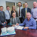 Deal for a decade! Chairman of Coastline Housing Derek Law MBE (left) and Blue Flame Director Mark Bolitho sign the 10-year contract, watched by (left