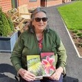 Henley House resident smiling with the floral donations