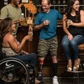 Photo of a group of people drinking in a pub including a woman in a wheelchair and a man with a prosthetic leg.