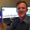 Founder, Dr. John Behr holding his mobile phone with newly launched app, and desktop version of the platform.