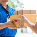 Picture of a delivery driver handing over parcels to a woman