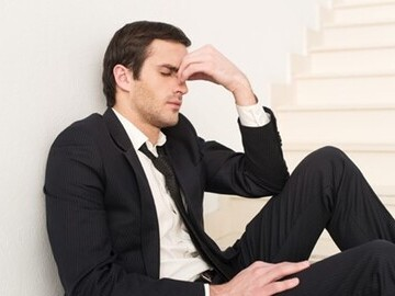 Man sat on stairs looking stressed