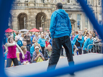DanceSyndrome Dance Leader and Trustee Peter Pamphlett  leads the crowd in a participation dance activity on the Royal Mile outdoor stage.