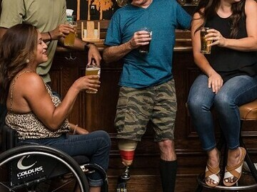 A group of friends enjoying a drink in a pub. Includes a woman in a wheelchair and a man with a prosthetic leg.