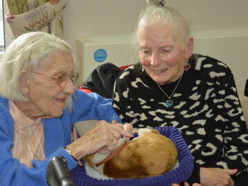 Residents Marigold Wilcock (left) and Shirley Blake enjoy giving some attention to a life-like puppy